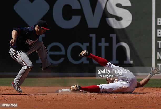 Xander Bogaerts of the Boston Red Sox attempts to steal second base as Brian Dozier of the Minnesota Twins awaits the umpire's call at Fenway Park on...