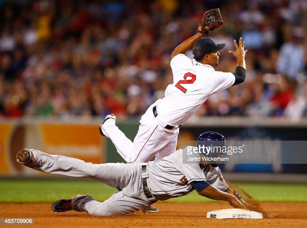 Xander Bogaerts of the Boston Red Sox attempts to turn the double play over Dexter Fowler of the Houston Astros during the game at Fenway Park on...
