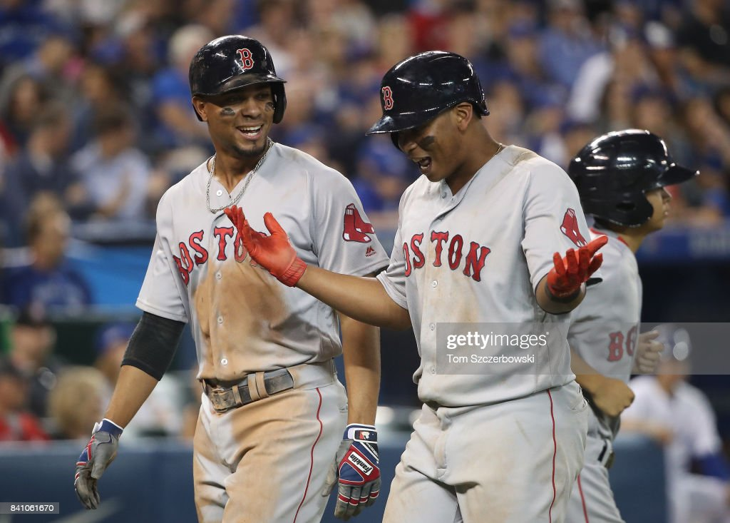 Xander Bogaerts #2 of the Boston Red Sox celebrates with Rafael Devers #11 after both scored on a single by Mitch Moreland in the eighth inning during MLB game action against the Toronto Blue Jays at Rogers Centre on August 30, 2017 in Toronto, Canada.