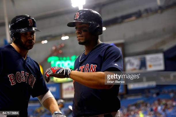 Xander Bogaerts of the Boston Red Sox celebrates with teammate Mitch Moreland as he makes his way to the dugout after scoring off of an RBI single by...
