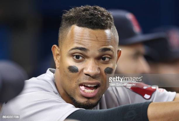 Xander Bogaerts of the Boston Red Sox chews gum as he talks to a teammate from the top step of the dugout during MLB game action against the Toronto...
