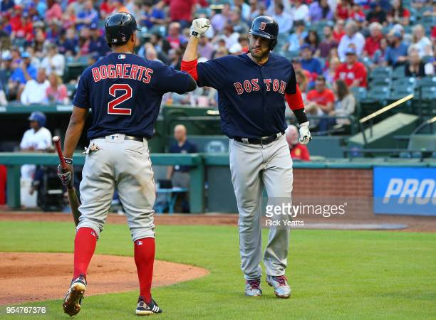 Xander Bogaerts of the Boston Red Sox congratulates JD Martinez for hitting a hits a solo home run in the first inning against the Texas Rangersat...