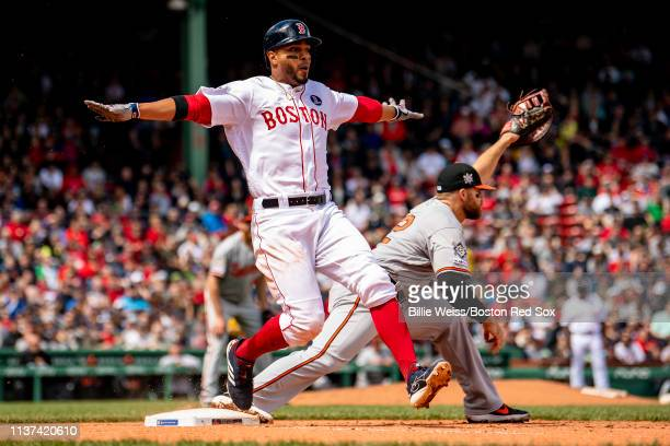 Xander Bogaerts of the Boston Red Sox gestures as he beats out an infield single caught by Chris Davis of the Baltimore Orioles during the fifth...