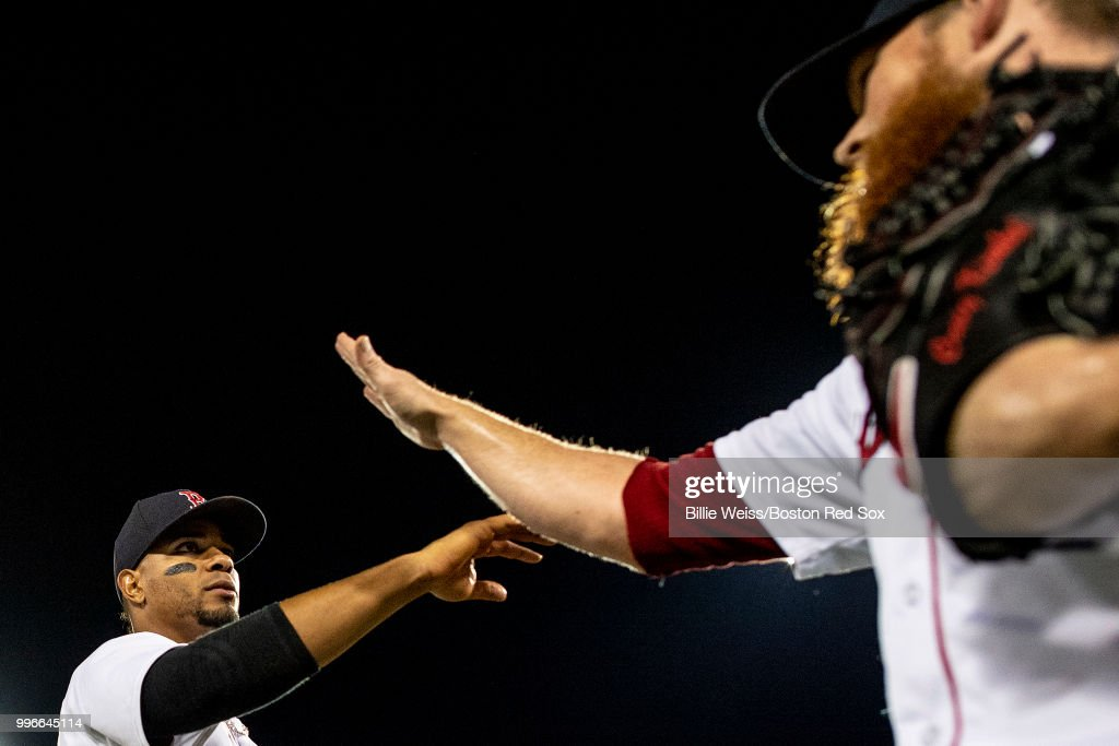 Xander Bogaerts #2 of the Boston Red Sox high fives Craig Kimbrel #46 after a game against the Texas Rangers on July 11, 2018 at Fenway Park in Boston, Massachusetts.