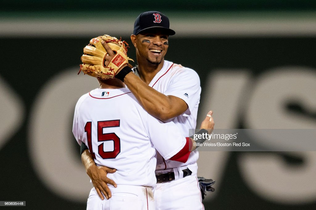 Xander Bogaerts #2 of the Boston Red Sox hugs Dustin Pedroia #15 after recording the final out of a game against the Toronto Blue Jays on May 29, 2018 at Fenway Park in Boston, Massachusetts.