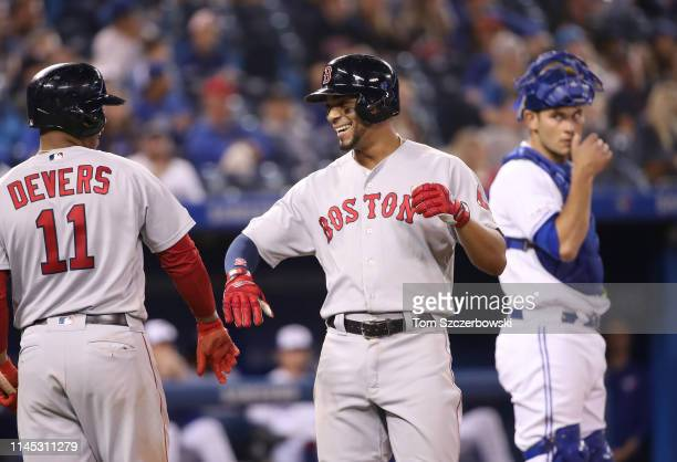 Xander Bogaerts of the Boston Red Sox is congratulated by Rafael Devers after hitting a solo home run in the ninth inning during MLB game action...