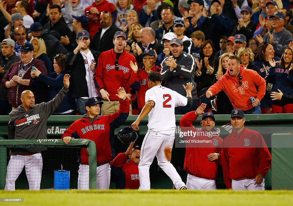 Xander Bogaerts #2 of the Boston Red Sox is congratulated by teammates in the dugout after scoring the game-tying run in the 8th inning against the Atlanta Braves during the game at Fenway Park on May 29, 2014 in Boston, Massachusetts.