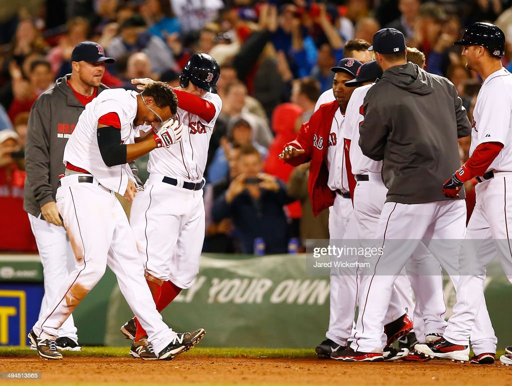 Xander Bogaerts #2 of the Boston Red Sox is mobbed by his teammates including Brock Holt #26 after hitting the walk-off game-winning RBI single in the 9th inning against the Atlanta Braves during the game at Fenway Park on May 29, 2014 in Boston, Massachusetts.