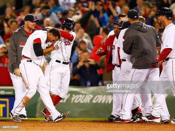 Xander Bogaerts of the Boston Red Sox is mobbed by his teammates including Brock Holt after hitting the walkoff gamewinning RBI single in the 9th...