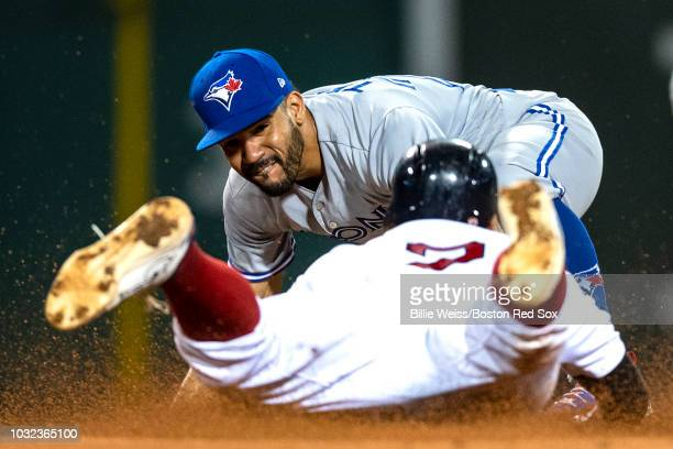 Xander Bogaerts of the Boston Red Sox is tagged out by Devon Travis of the Toronto Blue Jays during the fourth inning of a game on September 12 2018...