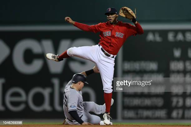 Xander Bogaerts of the Boston Red Sox jumps to avoid Luke Voit of the New York Yankees while turing the double play in the second inning of Game One...