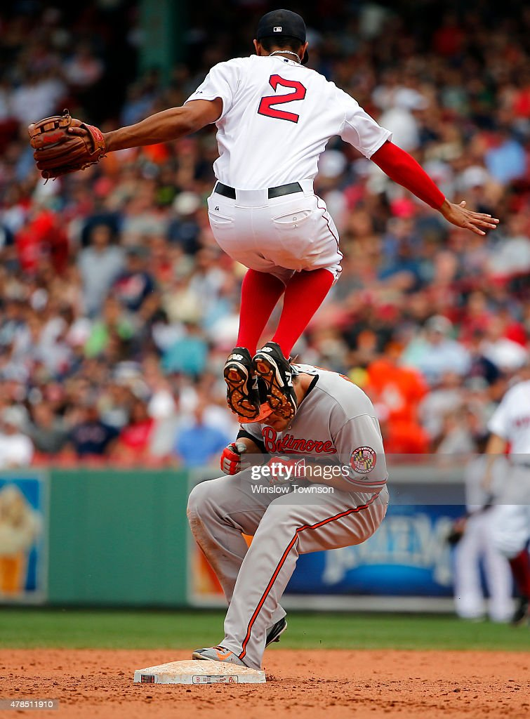 Xander Bogaerts #2 of the Boston Red Sox leaps to avoid Chris Davis #19 of the Baltimore Orioles after he doubled during the seventh inning in a game at Fenway Park on June 25, 2015 in Boston, Massachusetts.