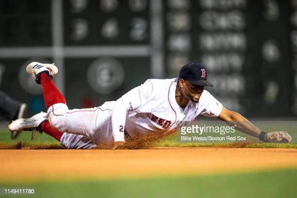 Xander Bogaerts of the Boston Red Sox makes a diving stop during the sixth inning of a game against the Texas Rangers on June 11 2019 at Fenway Park...