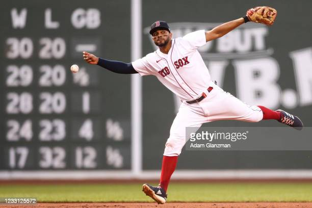 Xander Bogaerts of the Boston Red Sox misplays a ball in the second inning of a game against the Atlanta Braves at Fenway Park on May 26, 2021 in...