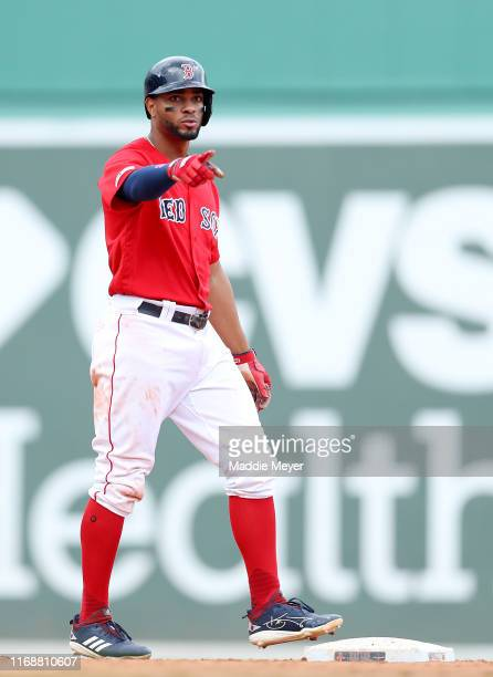 Xander Bogaerts of the Boston Red Sox points to JD Martinez after Martinez hit a single during the sixth inning against the Baltimore Orioles at...