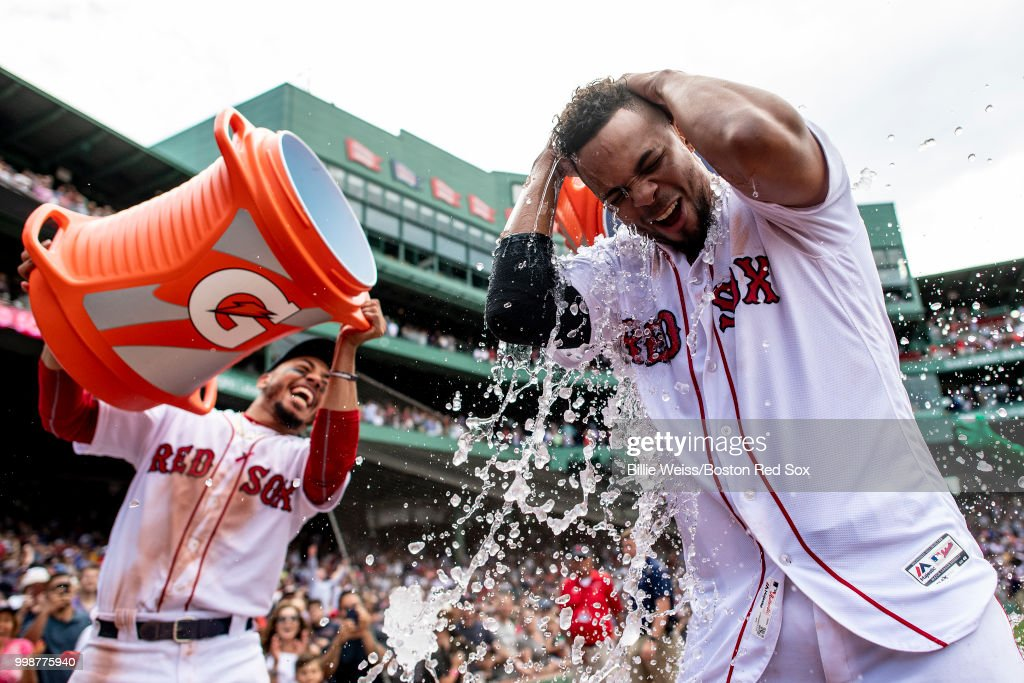 Xander Bogaerts #2 of the Boston Red Sox reacts as he is doused with Gatorade by Mookie Betts #50 after hitting a walk-off grand slam home run during the tenth inning of a game against the Toronto Blue Jays on July 14, 2018 at Fenway Park in Boston, Massachusetts.