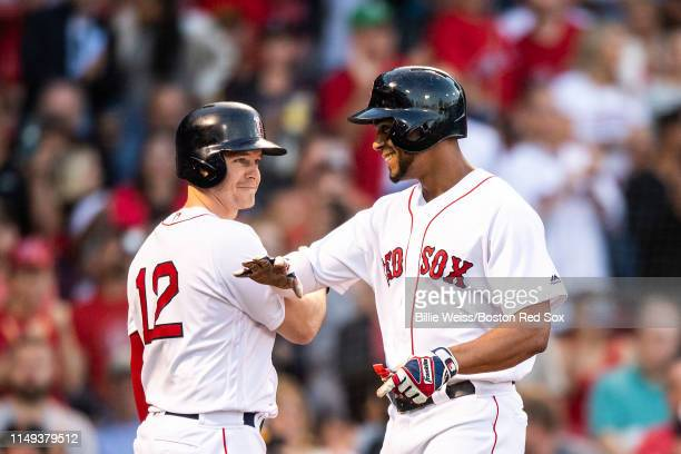Xander Bogaerts of the Boston Red Sox reacts with Brock Holt after hitting a solo home run during the first inning of a game against the Texas...