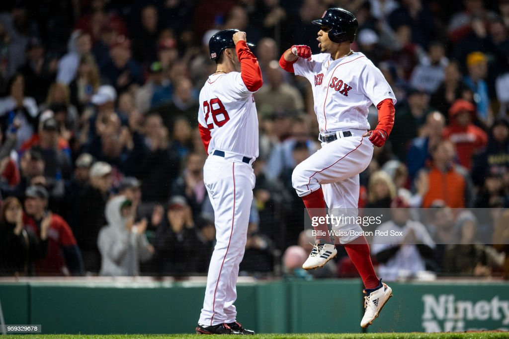 Xander Bogaerts #2 of the Boston Red Sox reacts with J.D. Martinez #28 after hitting a three run home run during the sixth inning of a game against the Oakland Athletics on May 16, 2018 at Fenway Park in Boston, Massachusetts.