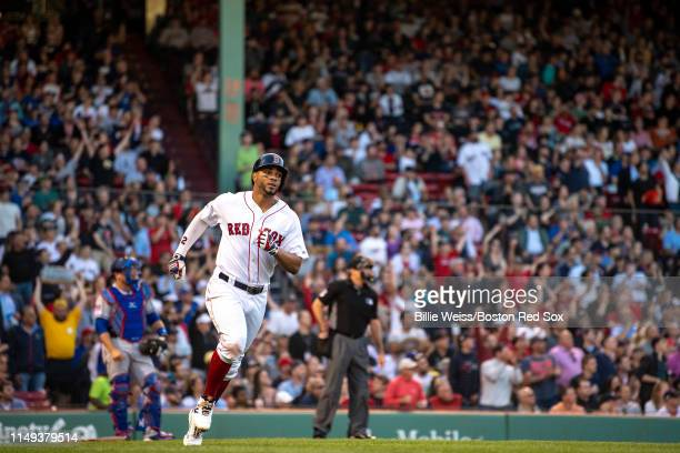 Xander Bogaerts of the Boston Red Sox rounds first base after hitting a solo home run during the first inning of a game against the Texas Rangers on...