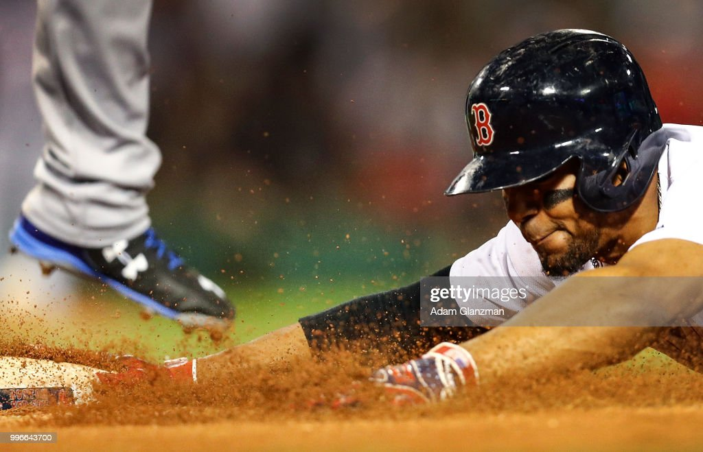 Xander Bogaerts #2 of the Boston Red Sox slides into first base under the foot of Ronald Guzman #67 of the Texas Rangers in the eighth inning a game against the Texas Rangers at Fenway Park on July 11, 2018 in Boston, Massachusetts.