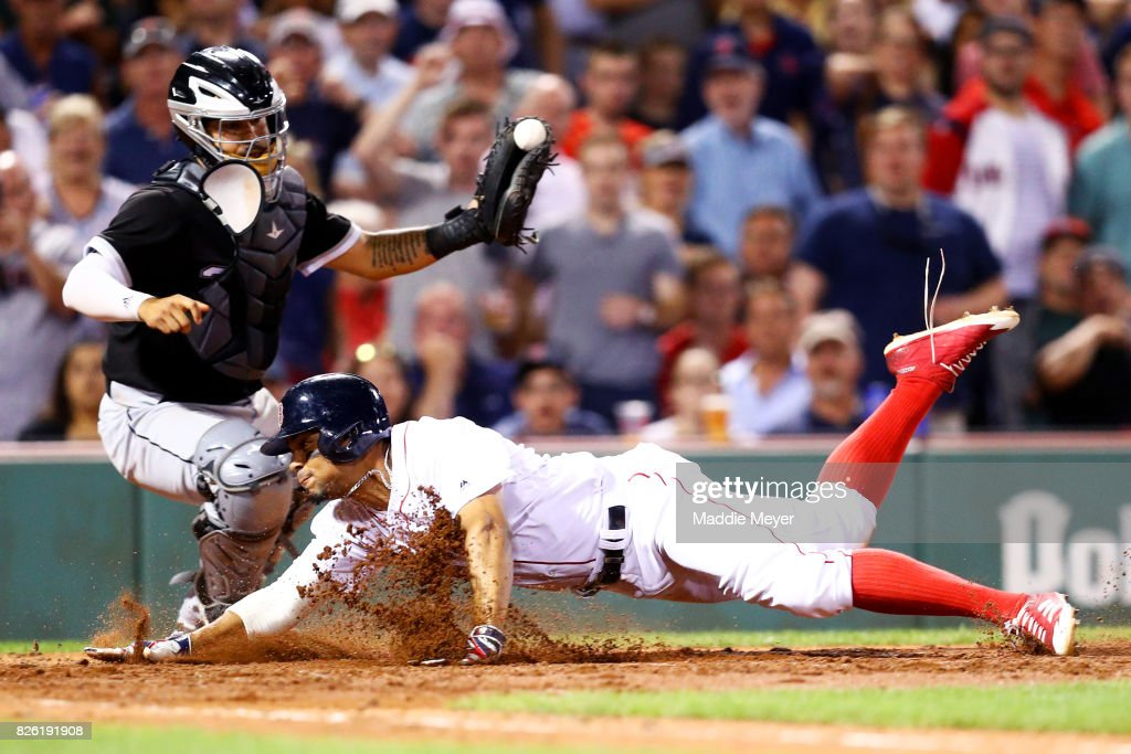 Xander Bogaerts #2 of the Boston Red Sox slides past Omar Narvaez #38 of the Chicago White Sox to score a run during the sixth inning at Fenway Park on August 2, 2017 in Boston, Massachusetts.