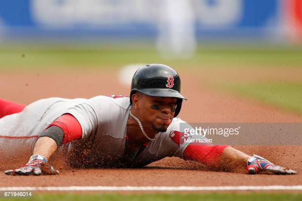 Xander Bogaerts of the Boston Red Sox slides safely into third base against the Baltimore Orioles in the first inning at Oriole Park at Camden Yards...