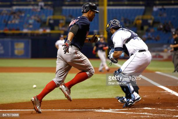 Xander Bogaerts of the Boston Red Sox sprints home to score ahead of catcher Wilson Ramos of the Tampa Bay Rays off of the RBI single by Andrew...
