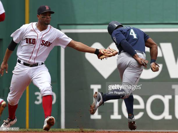 Xander Bogaerts of the Boston Red Sox tags out Denard Span of the Seattle Mariners who was caught off of first base in the third inning at Fenway...