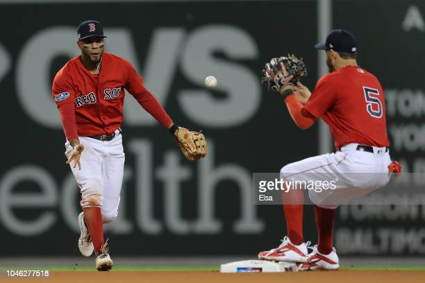 Xander Bogaerts of the Boston Red Sox tosses the ball to Ian Kinsler to make the force out at second against the New York Yankees in the sixth inning...