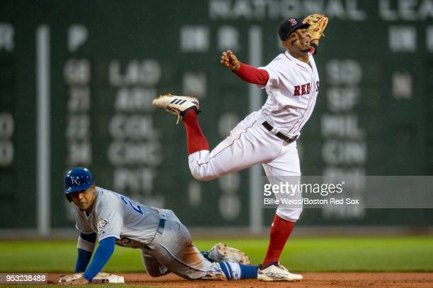 Xander Bogaerts of the Boston Red Sox turns a double play over Jon Jay of the Kansas City Royals during the first inning of a game on April 30 2018...