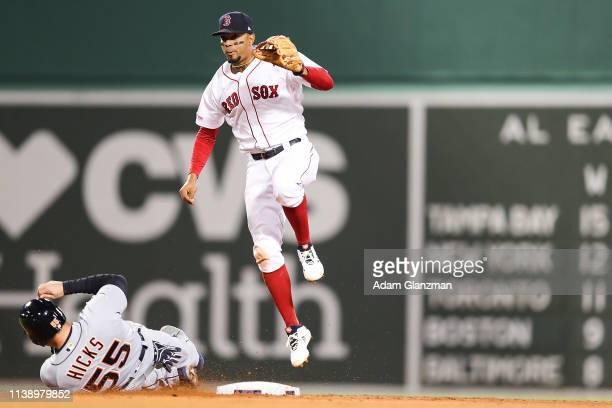 Xander Bogaerts of the Boston Red Sox turns a double play over the slide of John Hicks of the Detroit Tigers in the third inning of the second game...