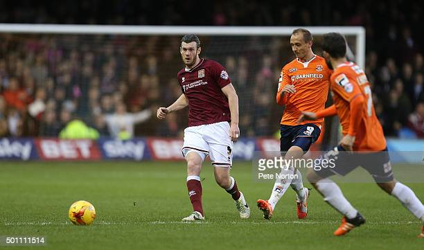 Xander Diamond of Northampton Town plays the ball watched by Paul Benson of Luton Town during the Sky Bet League Two match between Luton Town and...