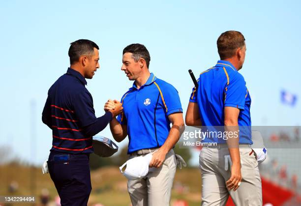 Xander Schauffele of team United States and Rory McIlroy of Northern Ireland and team Europe shake hands on the 15th green during Friday Morning...