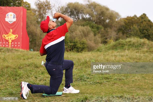 Xander Schauffele of team United States celebrates their 19 to 9 win over Team Europe with a drink during Sunday Singles Matches of the 43rd Ryder...