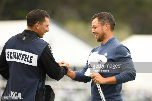Xander Schauffele of the United States and his caddie Austin Kaiser shake hands on the 18th green during the first round of the 2019 US Open at...