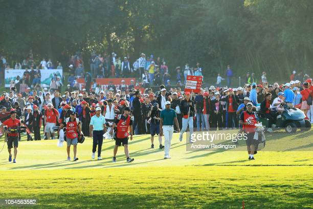 Xander Schauffele of the United States and Tony Finau of the United States walk on the 18th hole during the final round of the WGC HSBC Champions at...