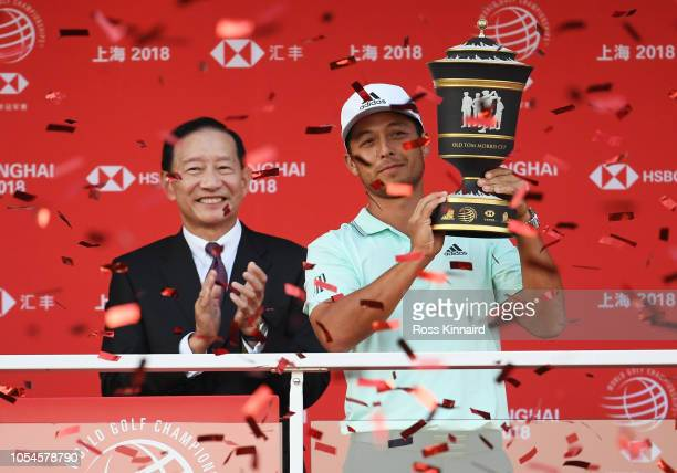 Xander Schauffele of the United States celebrates with the winner's trophy and Chief Executive of HSBC, Peter Wong, on the Champion's Balcony after...