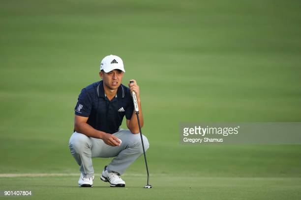 Xander Schauffele of the United States lines up a putt on the 18th green during the first round of the Sentry Tournament of Champions at Plantation...