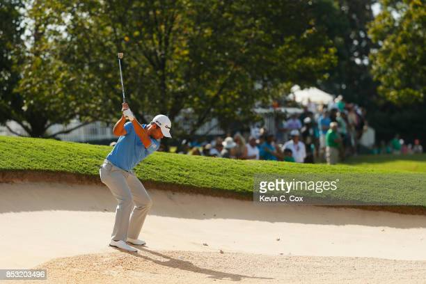Xander Schauffele of the United States plays a shot from a bunker on the 12th hole during the final round of the TOUR Championship at East Lake Golf...