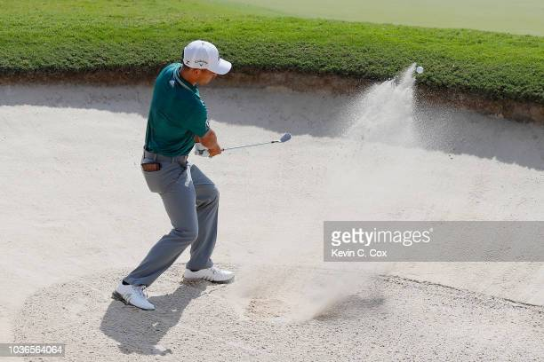 Xander Schauffele of the United States plays a shot from a greenside bunker on the first hole during the first round of the TOUR Championship at East...