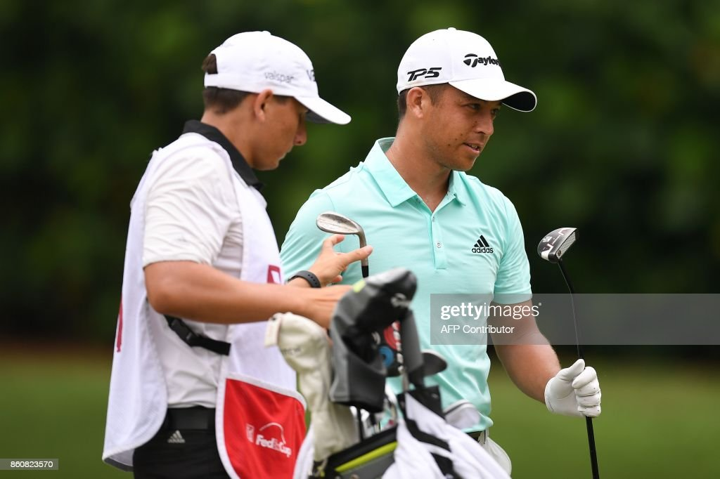 Xander Schauffele of the US (R) exchanges his club after playing a shot on the first hole fairway during the second round of the 2017 CIMB Classic golf tournament in Kuala Lumpur on October 13, 2017. /