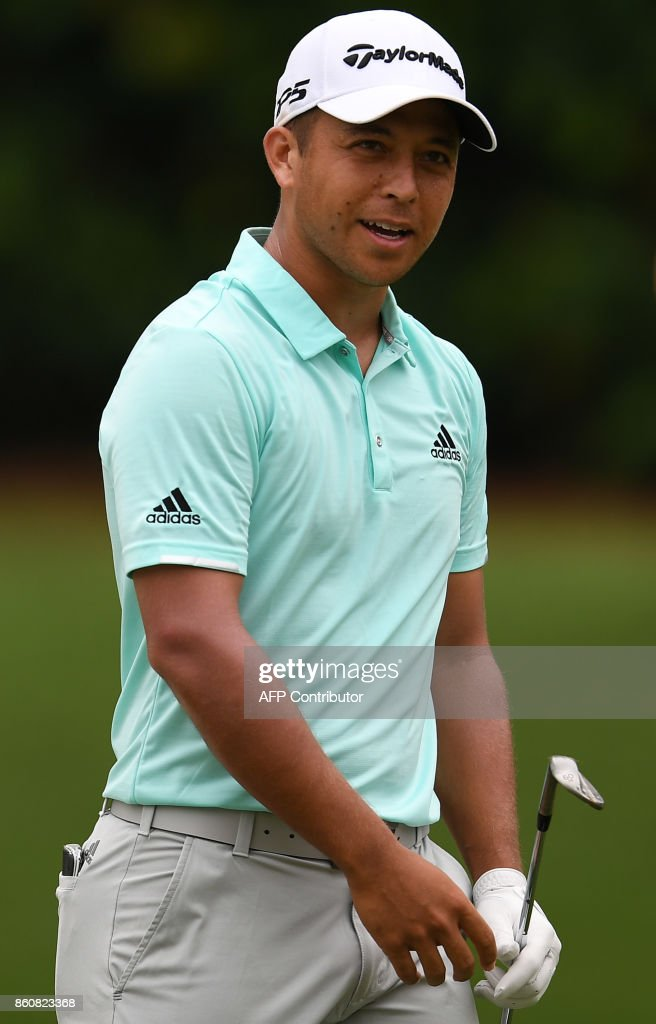Xander Schauffele of the US smiles after playing a shot on the first hole fairway during the second round of the 2017 CIMB Classic golf tournament in Kuala Lumpur on October 13, 2017. /