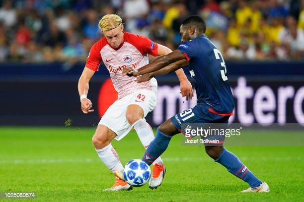 Xaver Schlager of FC Salzburg and El Fardou Ben Nabouhane of Belgrade compete for the ball during the UEFA Champions League match between FC Salzburg...