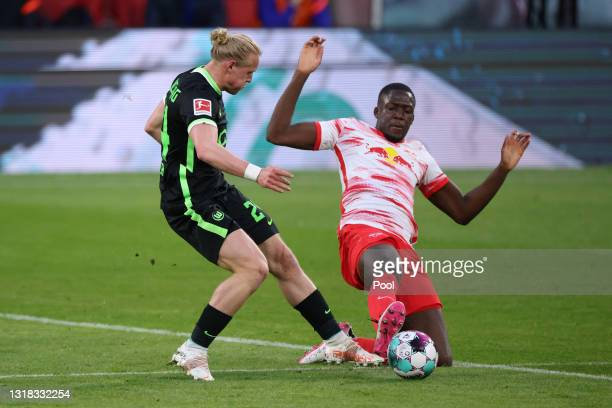 Xaver Schlager of VfL Wolfsburg is challenged by Ibrahima Konate of RB Leipzig during the Bundesliga match between RB Leipzig and VfL Wolfsburg at...