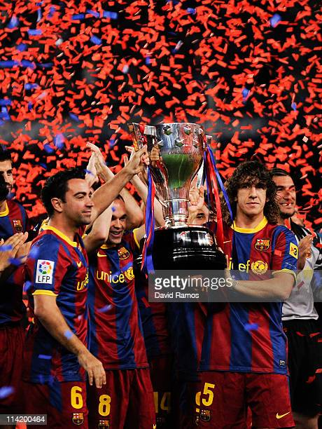 Xavi Hernandez and Carles Puyol of FC Barcelona hold aloft the La Liga trophy after the La Liga match between Barcelona and Deportivo La Coruna at...