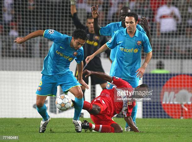 Xavi Hernandez and his team mate Andres Iniesta of Barcelona challenge for the ball with Cacau of Stuttgart during the UEFA Champions League Group E...