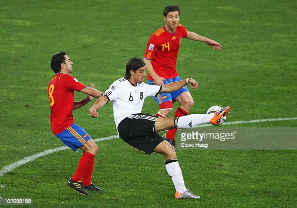 Xavi Hernandez and Xabi Alonso of Spain challenge Sami Khedira of Germany during the 2010 FIFA World Cup South Africa Semi Final match between...