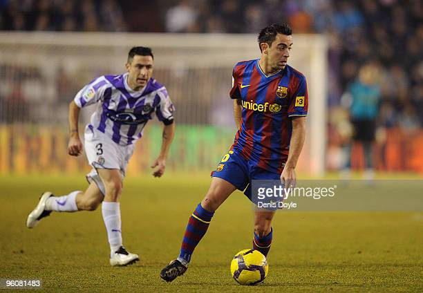 Xavi Hernandez of Barcelona controls the ball while being watched by Alberto Marcos of Valladolid during the La Liga match between Valladolid and...