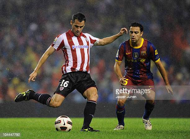 Xavi Hernandez of Barcelona duels for the ball with Pablo Orbaiz of Athletic Bilbao during the La Liga match between Athletic Bilbao and Barcelona at...