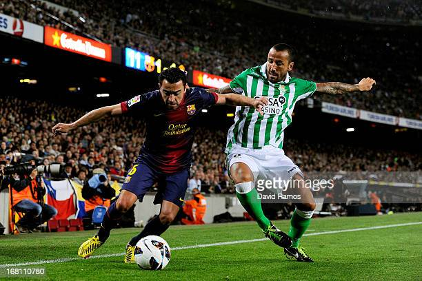 Xavi Hernandez of Barcelona holds off the challenge from Mario of Real Betis during the La Liga match between FC Barcelona and Real Betis Balompie at...